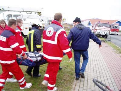 Angehörige der Freiwilligen Feuerwehr Zorbau und Rettungssanitäter bringen den Verletzten zum Krankenwagen.